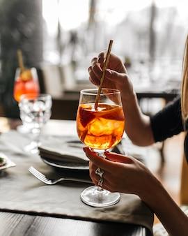 Frau, die aperol-spritz-cocktail mit einem strohhalm von einem glas trinkt