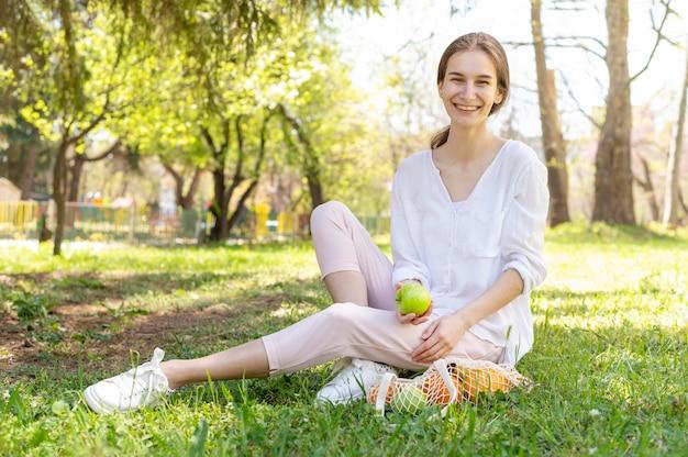 Frau, die apfel hält auf gras sitzt