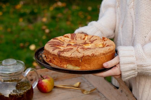 Frau, die apfelkuchen und tee auf behälter auf tabelle in einem garten hält