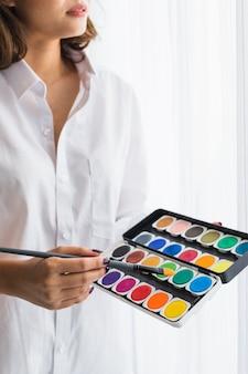 Frau, die aquarellfarben in den händen hält