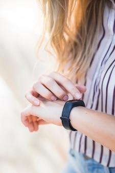 Frau, die armbanduhr auf ihrer hand betrachtet