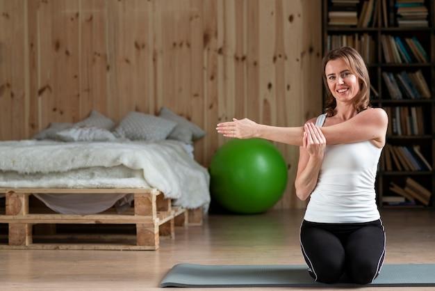 Frau, die arme auf yogamatte streckt