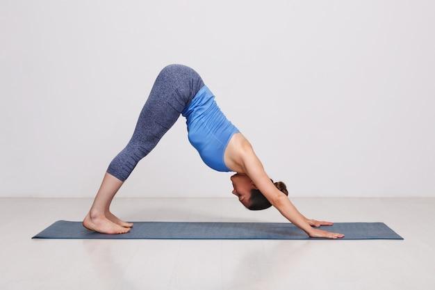 Frau, die ashtanga vinyasa yoga asana adhomukha svanasana tut