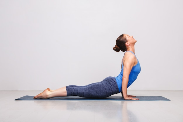 Frau, die ashtanga vinyasa yoga sonnengruß asana urdhva mu tut