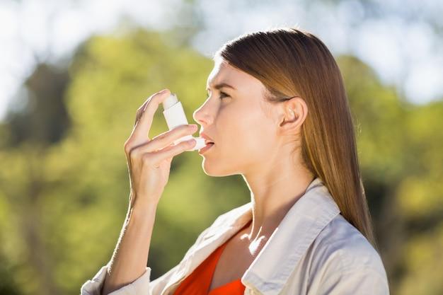 Frau, die asthmainhalator verwendet