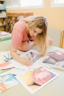 Frau, die auf arbeitsbankmalerei mit farbigem bleistift auf leinwandpapier sitzt
