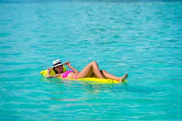 Frau, die auf aufblasbarer luftmatratze am türkiswasser sich entspannt