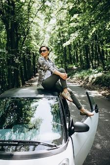 Frau, die auf autodach im wald sitzt
