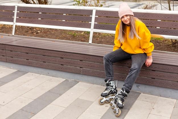 Frau, die auf bank beim tragen von rollenblättern sitzt