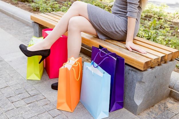 Frau, die auf bank mit multi farbigen einkaufstaschen sitzt