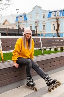 Frau, die auf bank mit rollenblättern lächelt und aufwirft