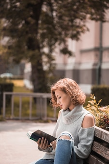 Frau, die auf bank- und lesebuch im park sitzt