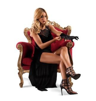 Frau, die auf barockem sessel sitzt, der handschuhe trägt