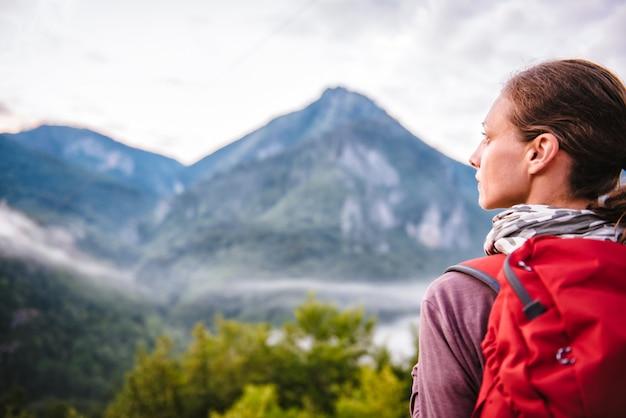 Frau, die auf berg steht und seitlich schaut