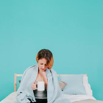 Frau, die auf bett krank sich fühlt