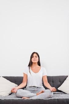 Frau, die auf bett meditiert