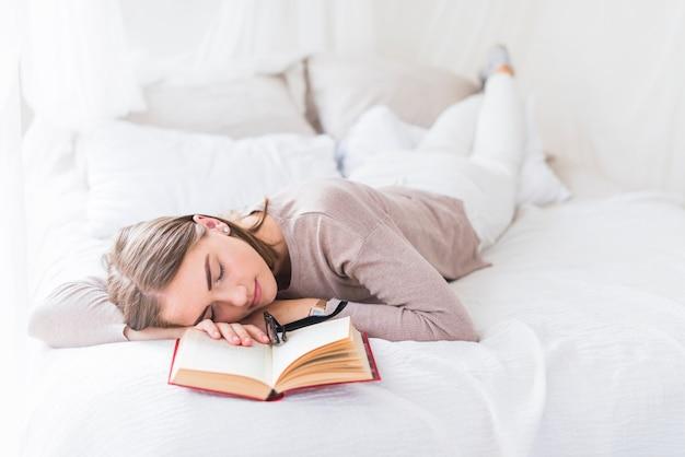 Frau, die auf bett mit brillen über dem offenen buch schläft