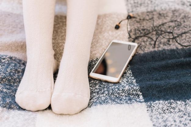 Frau, die auf bett mit smartphone liegt