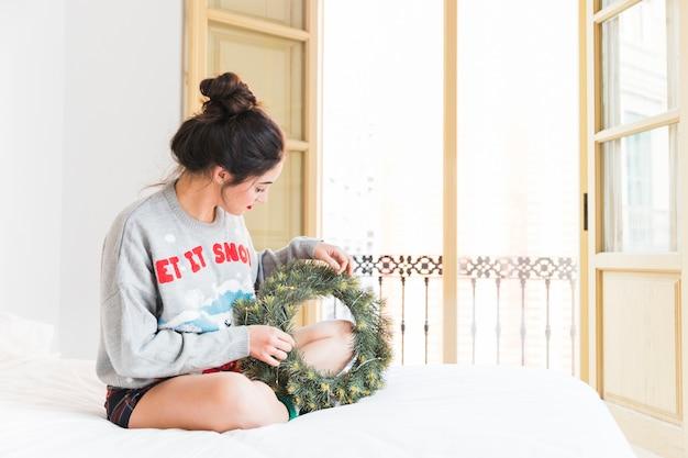 Frau, die auf bett mit weihnachtskranz sitzt