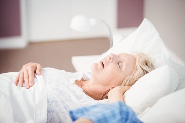 Frau, die auf bett nahe bei ehemann schnarcht