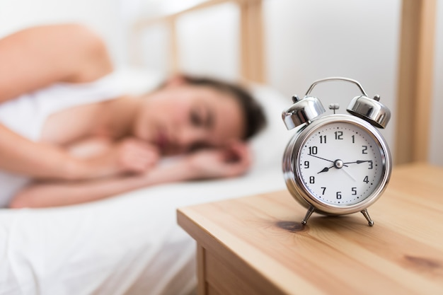 Frau, die auf bett nahe wecker auf hölzernem schreibtisch schläft