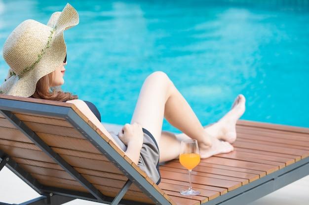 Frau, die auf bett neben swimmingpool sitzt