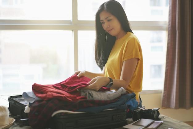 Frau, die auf bett sitzt und kleidung in der koffertasche im schlafzimmer packen