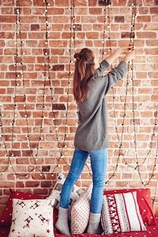 Frau, die auf bett steht und weihnachtslichter hängt