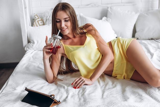 Frau, die auf bett unter verwendung der tablette und des trinkens liegt