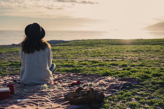 Frau, die auf bettdecke auf gras sitzt