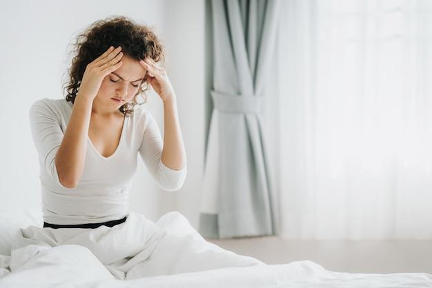 Frau, die auf bettgefühlkopfschmerzen sitzt