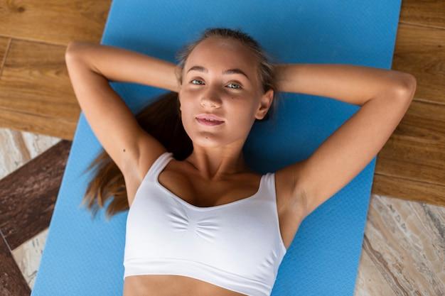 Frau, die auf blauer yogamatte liegt