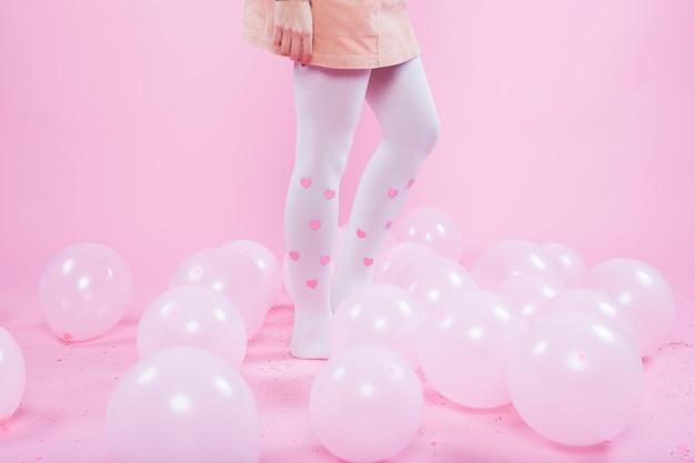 Frau, die auf boden mit ballonen steht