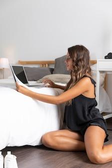 Frau, die auf boden mit laptop auf bett sitzt
