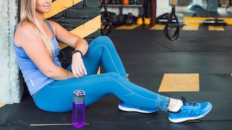 Frau, die auf Boden nahe Wasserflasche in der Turnhalle sitzt