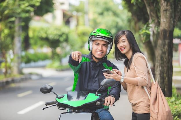 Frau, die auf bürgersteig spricht und motorradtaxi bestellt