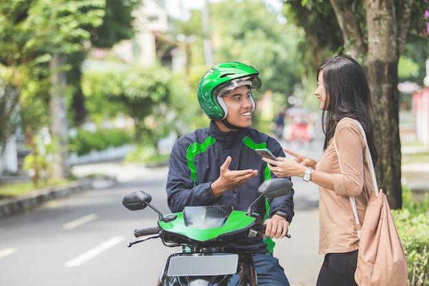 Frau, die auf bürgersteig steht, der ein kommerzielles motorradtaxi bestellt