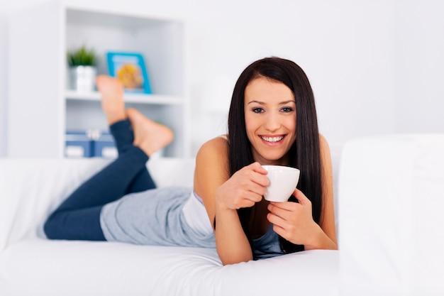 Frau, die auf couch mit tasse kaffee entspannt