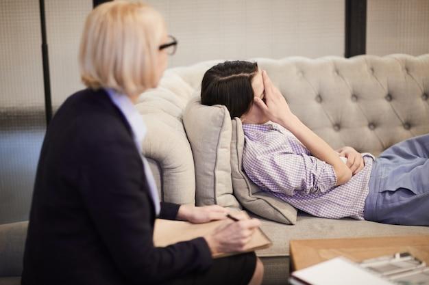 Frau, die auf couch während der therapiesitzung liegt