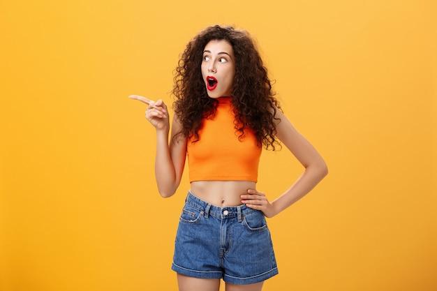 Frau, die auf das fenster der nachbarn späht und überrascht und erstaunt ist, zeigt und starrt sprachlos nach links über orangefarbenem hintergrund mit fallendem kiefer, fasziniert und begeistert im abgeschnittenen oberteil.