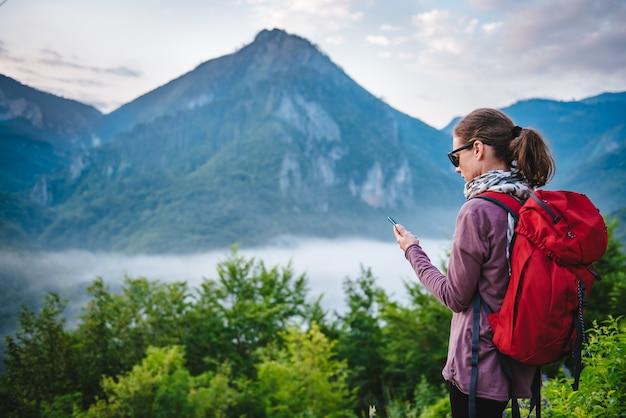 Frau, die auf dem berg wandert und intelligentes telefon verwendet
