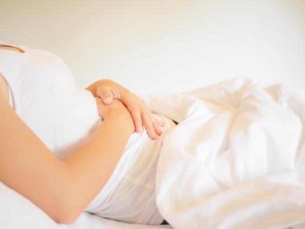 Frau, die auf dem bett hat magenschmerzen oder menstruationsschmerz liegt.