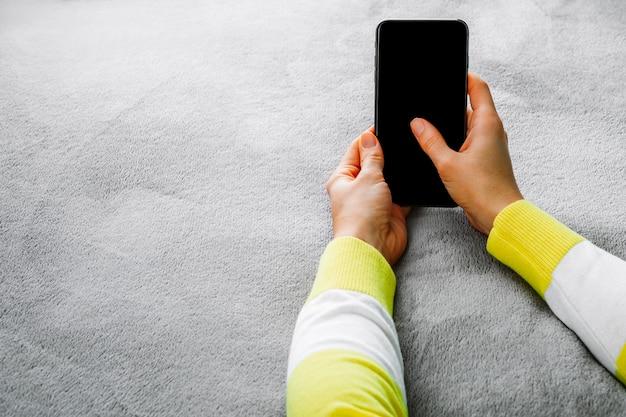Frau, die auf dem bett liegt und in der hand smartphone hält.