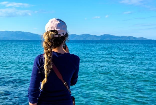 Frau, die auf dem blauen meer der kleinen kamera im dorf nea roda, chalkidiki, griechenland schießt