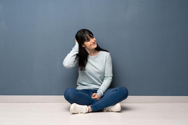 Frau, die auf dem boden denkt eine idee beim verkratzen des kopfes sitzt
