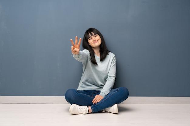 Frau, die auf dem boden glücklich sitzt und drei mit den fingern zählt