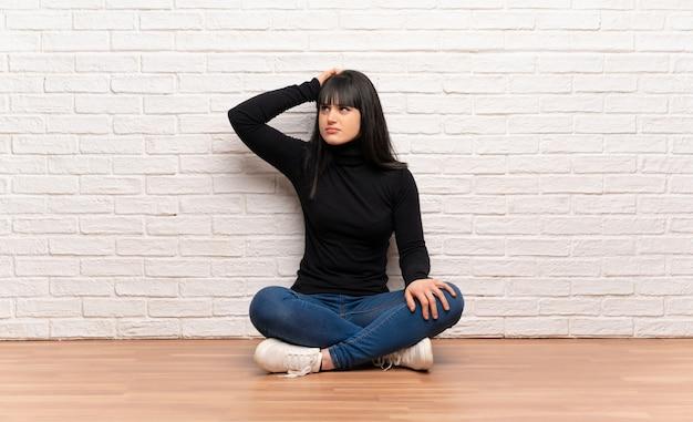 Frau, die auf dem boden hat zweifel beim verkratzen des kopfes sitzt