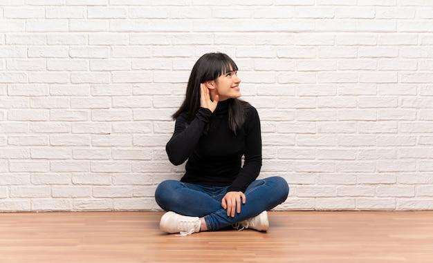 Frau, die auf dem boden hört zu etwas sitzt, indem sie hand auf das ohr setzt