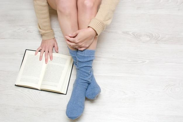 Frau, die auf dem boden liest eine buchdraufsicht und einen kopienraum sitzt