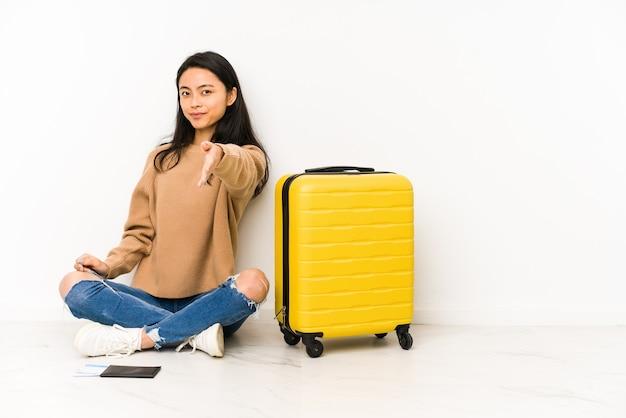 Frau, die auf dem boden mit einem koffer sitzt